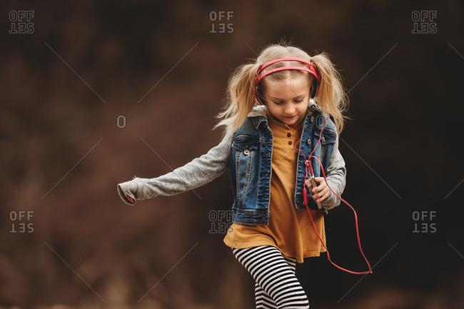 Blonde girl dancing while listening to headphones