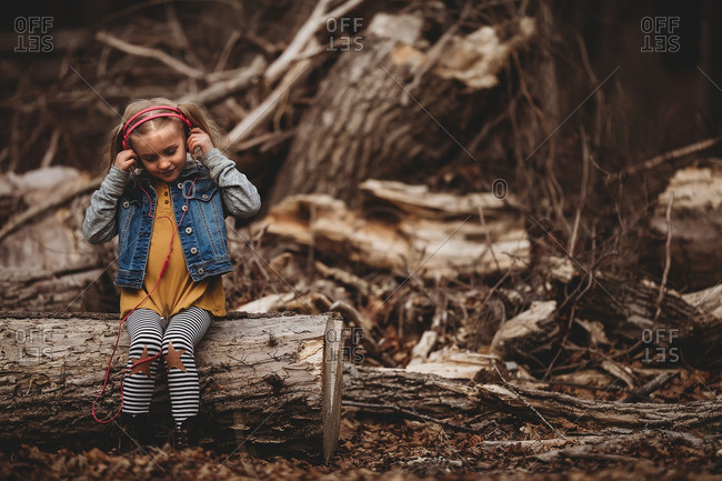 Young girl sitting on fallen tree log listening to music