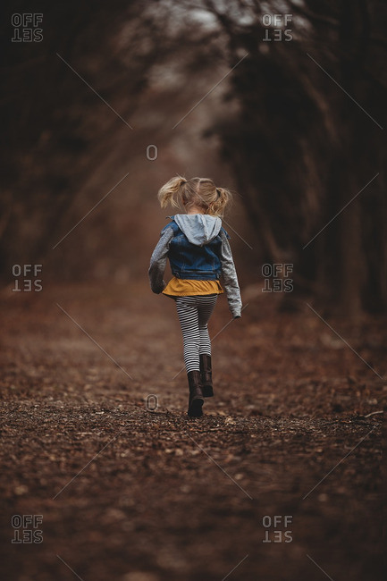 Blonde girl walking down a trail in the forest