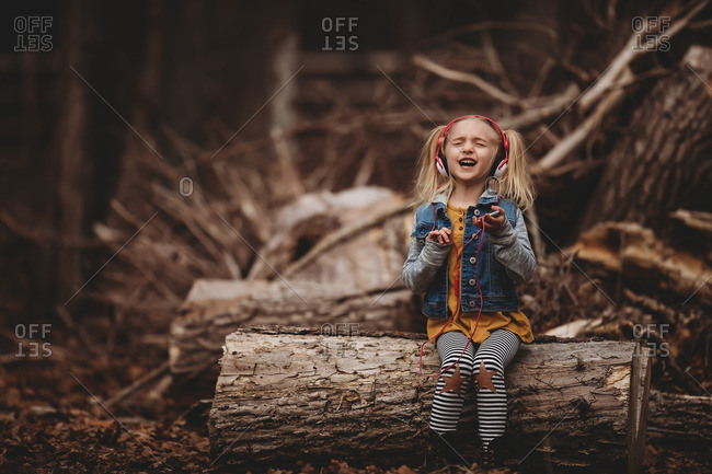 Young girl sitting on fallen tree log singing along to music