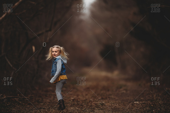 Little blonde girl looking back on a trail in the forest