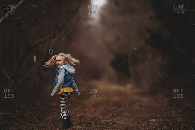 Blonde girl looking back on a trail in the forest