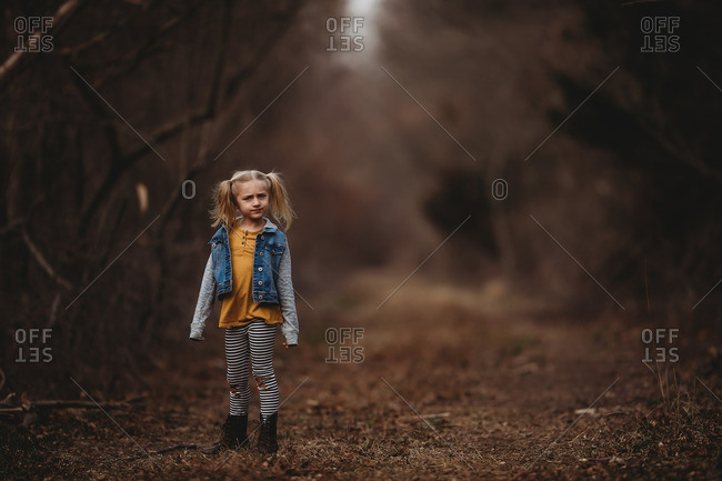 Little blonde girl with a confused look on a trail in the forest