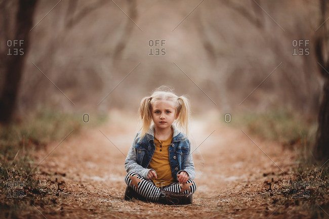 Little blonde girl sitting on a trail in the forest