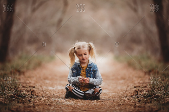 Young blonde girl sitting on a trail in the forest