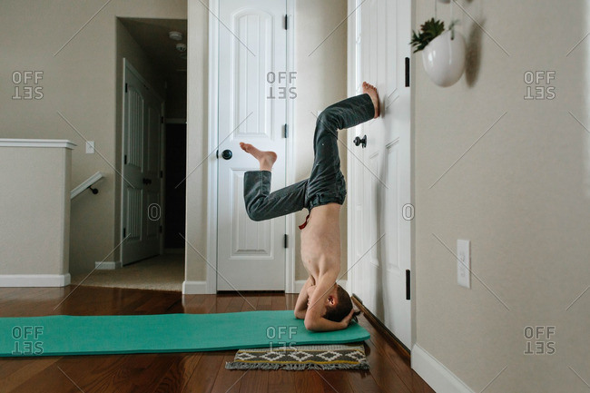 Boy doing headstand against a door