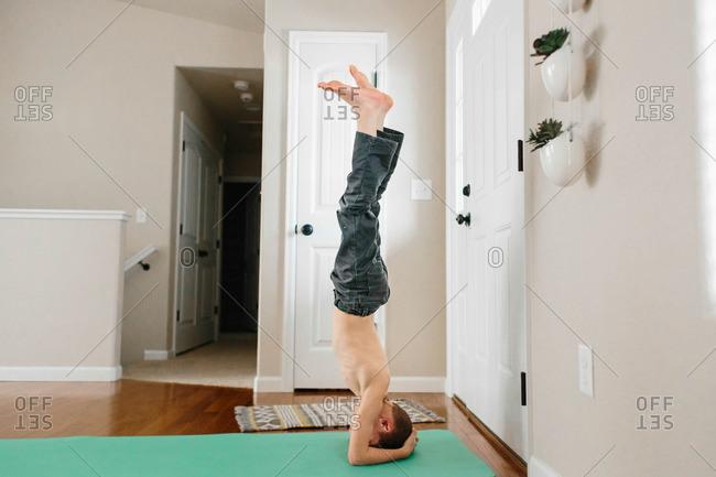 Little boy doing a headstand on a mat indoors