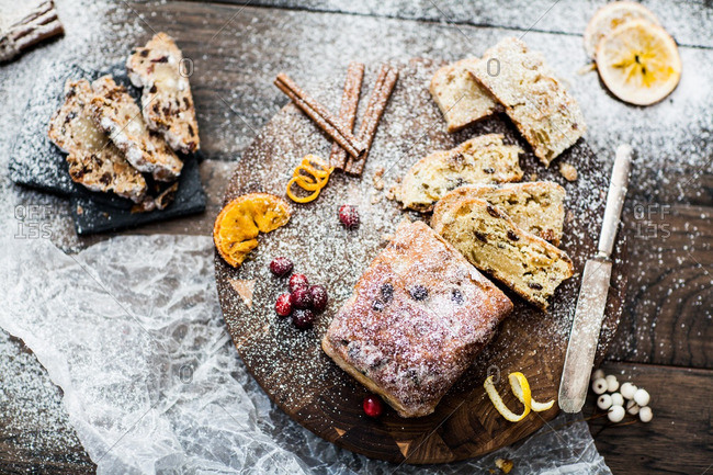 Stollen bread on a cutting board with berries and cinnamon