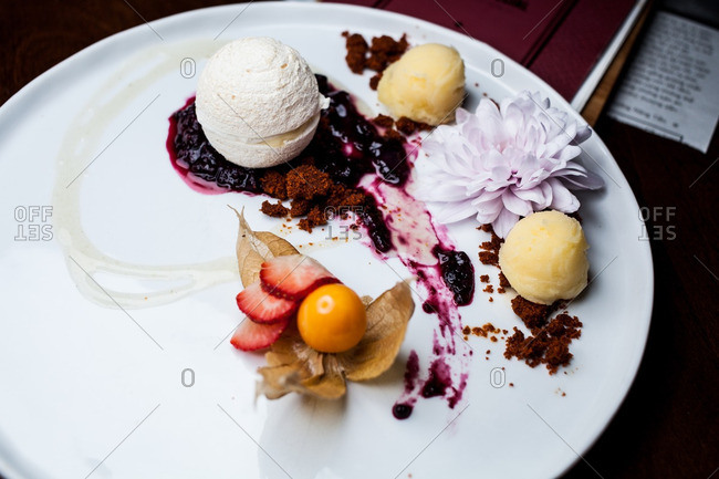 Ice cream served on a plate with fruit and flower in a restaurant