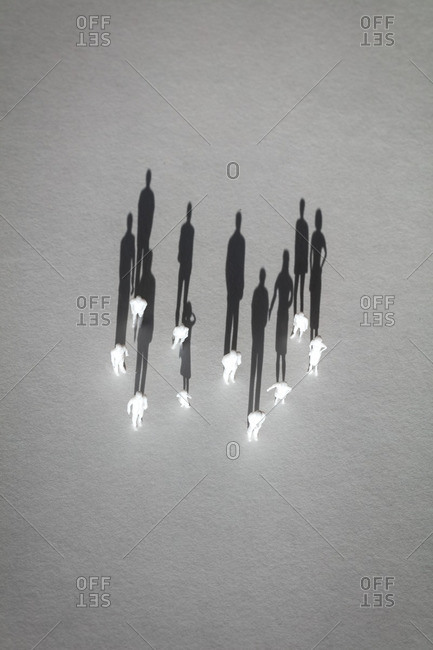 Overhead view of human figurines on white background with shadows