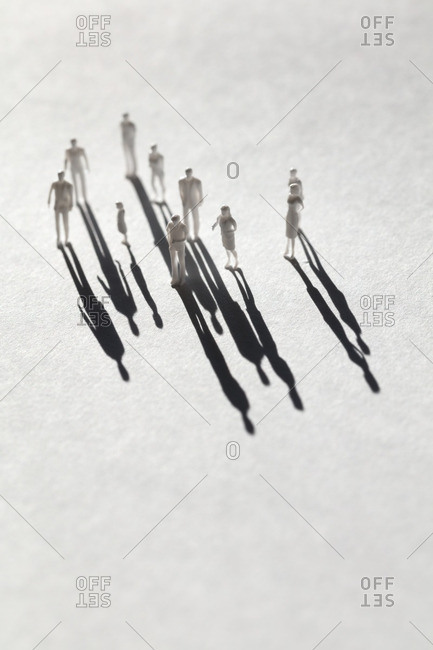 Plastic human figurines with shadows on white background