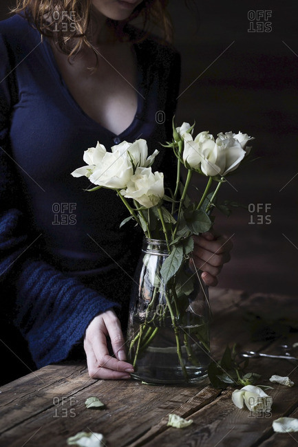 White roses on wooden table and woman on the background