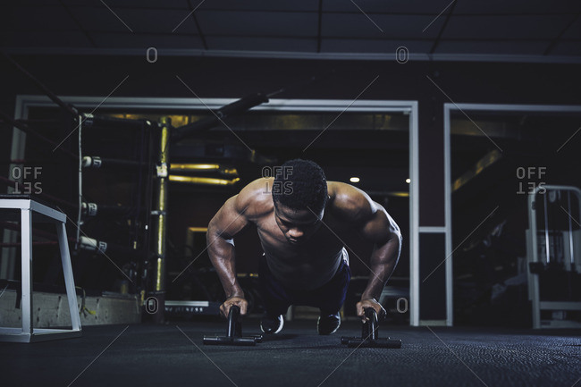 Determined male athlete doing pushups at gym