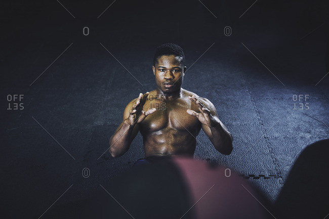 Portrait of determined male athlete working out with medicine ball at gym