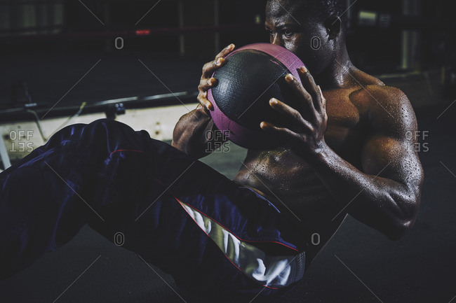 Dedicated male athlete holding medicine ball while doing sit-ups at gym
