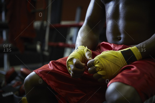 Midsection of boxer with hands wrapped in bandages sitting at health club