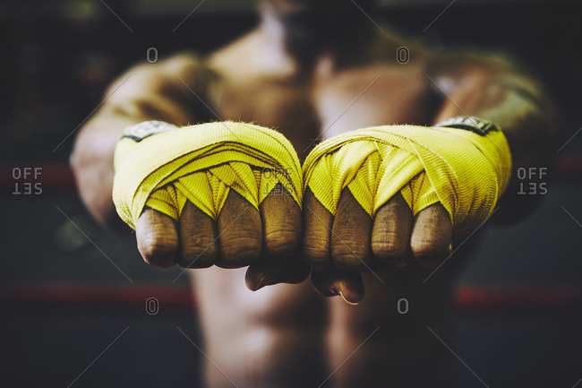 Midsection of boxer showing hands wrapped with bandages at health club