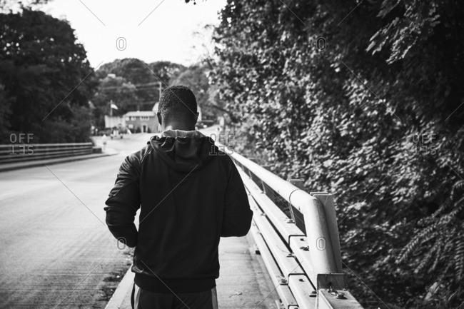 Rear view of male athlete jogging on sidewalk