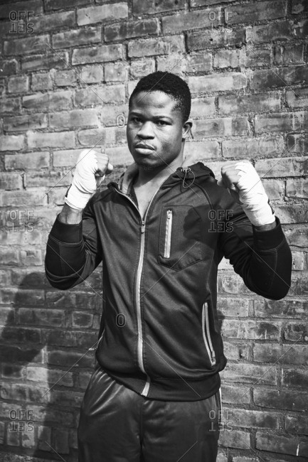 Portrait of confident boxer standing against brick wall