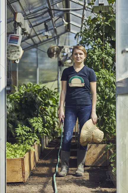 Full length portrait of confident female farmer standing in greenhouse