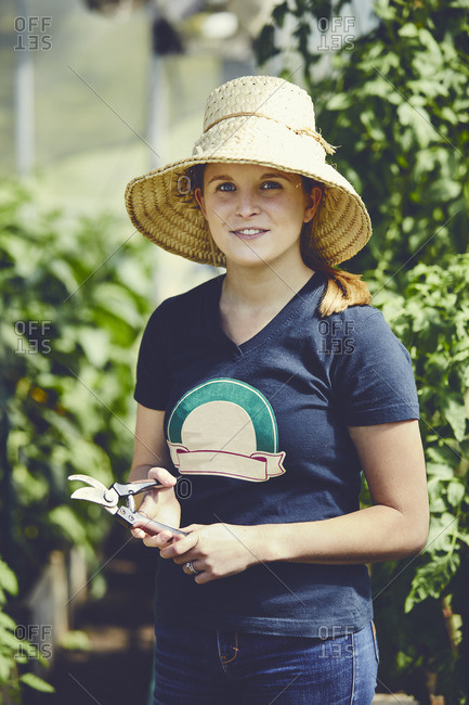 Portrait of confident female farmer holding pliers in greenhouse