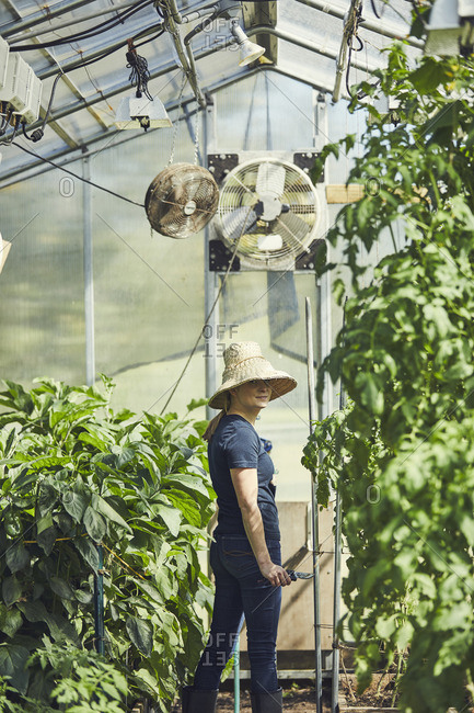 Side view portrait of woman standing in greenhouse