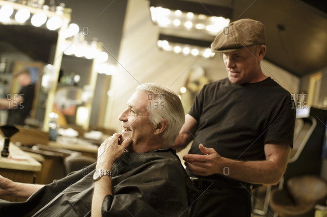 Side view of happy senior man receiving haircut from barber at shop