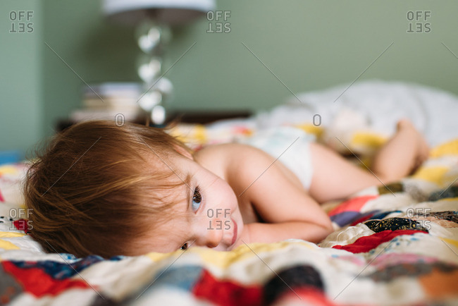 Toddler girl resting on a colorful vintage quilt on a bed
