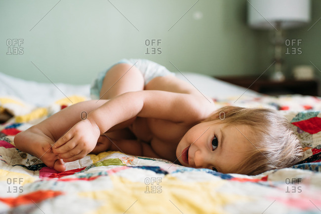 Toddler girl resting on a colorful vintage quilt and smiling