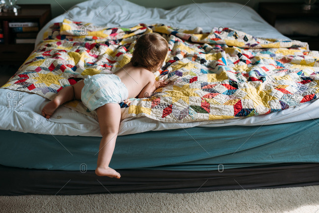 Toddler girl climbing off a bed with a vintage quilt