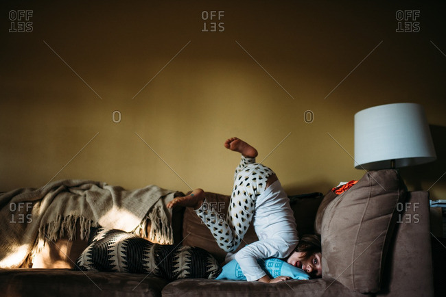 Girl playing on a couch with her legs up in the air