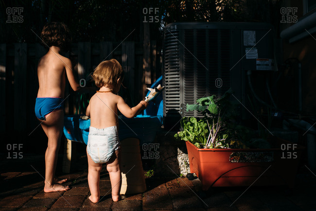 Two sisters playing outside at a water table