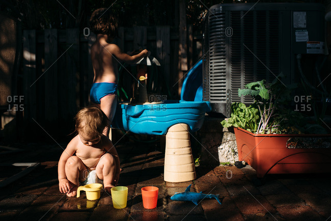 Two sisters playing with cups and toys at a water table outside