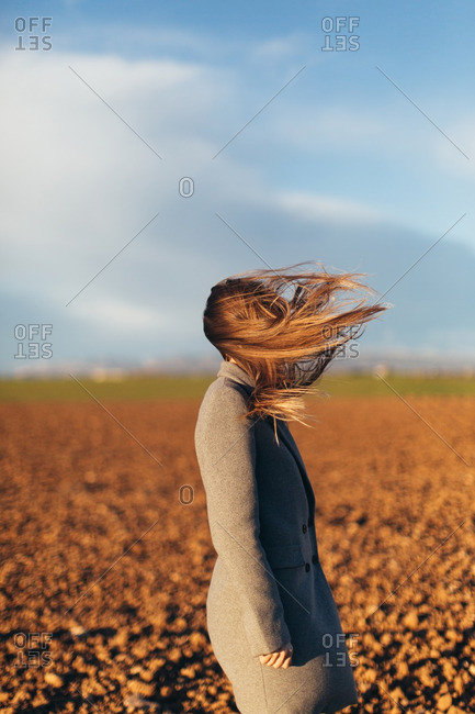 Woman standing in a field with her hair blowing in wind
