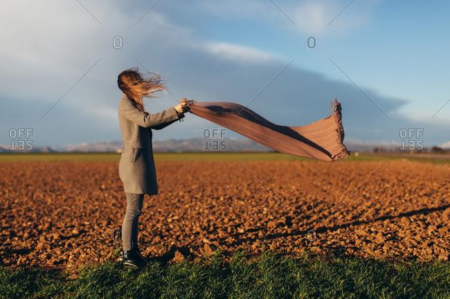 Woman in field unfurling a scarf in the wind