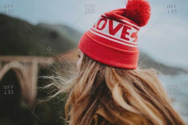 Blond woman in red hat gazes at bridge in Big Sur