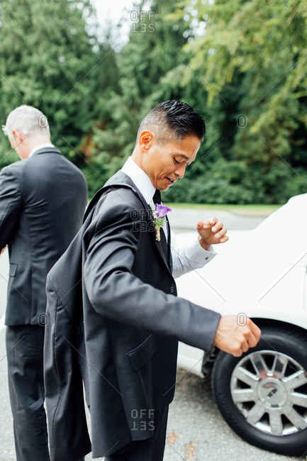 Two grooms getting dressed outside