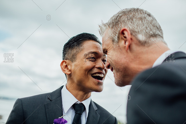 Grooms laughing in loving stare