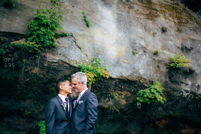 Grooms in loving gaze by coastal cliff
