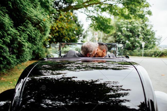 Grooms kissing in open top car