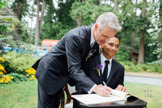 Grooms signing a book at outdoor wedding
