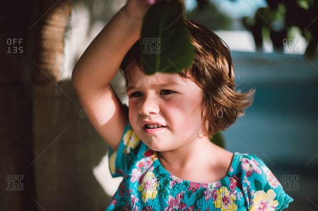 Brown haired girl holding leaf