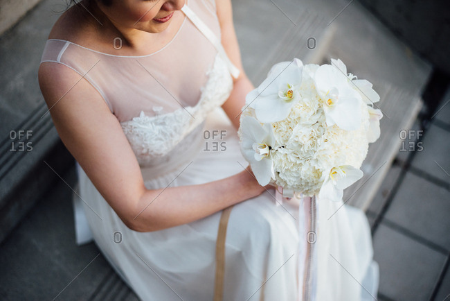 Bride on steps with white flowers