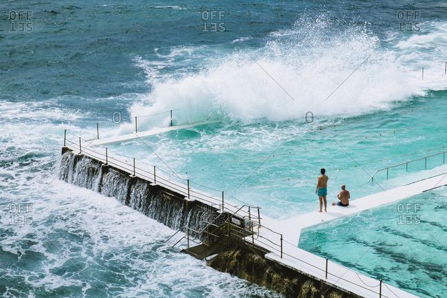 People at pool by waves on Bondi Beach
