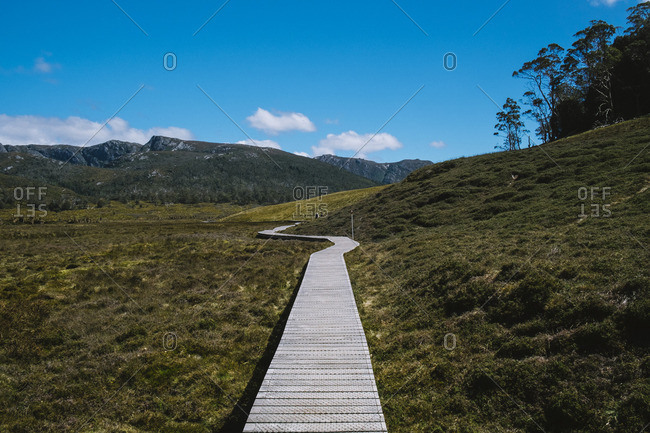 Walkway in prairie near mountains