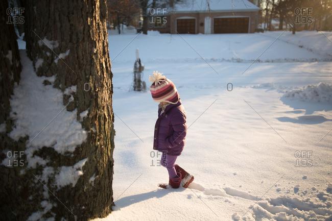 Girl strolling through snowy yard