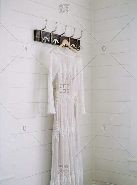 Vintage wedding dress hanging from hooks on a wall
