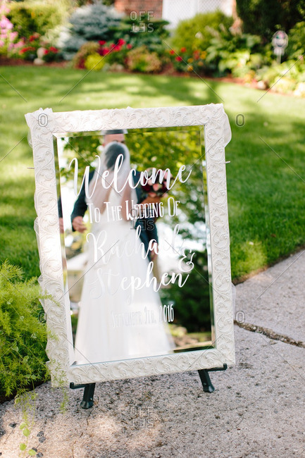 Reflection of bride and groom in the welcome sign to their wedding