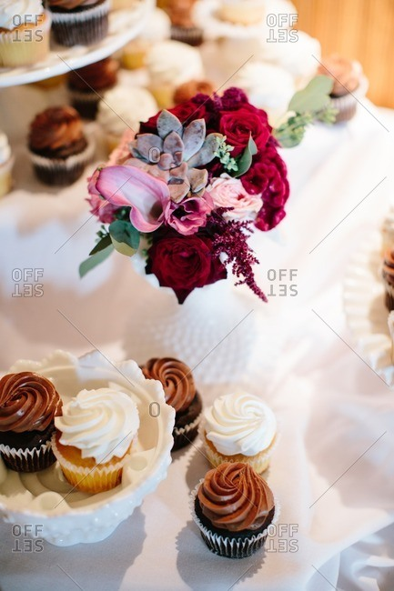 Cupcakes by flowers at a wedding