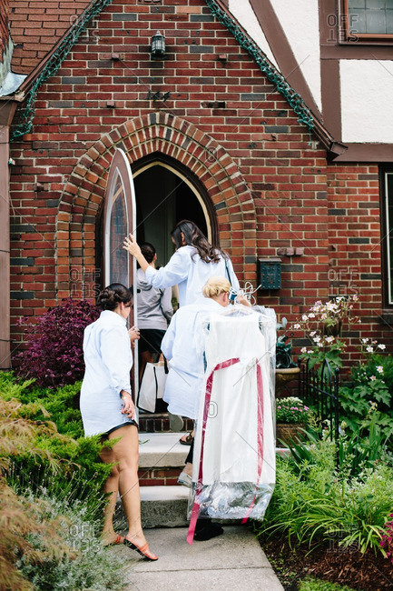 Bridal party walking into brick house carrying dresses